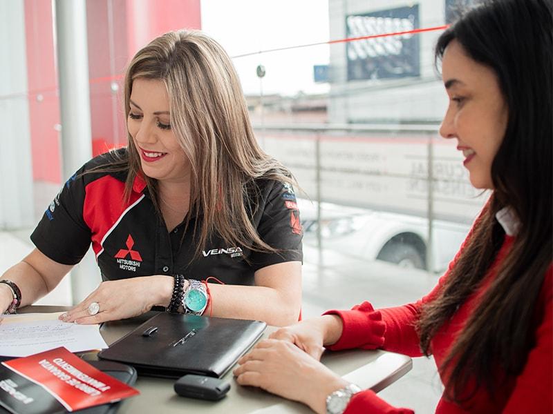 Vendedora de autos y clienta llenando documentos - Somos Veinsa - Veinsa Motors